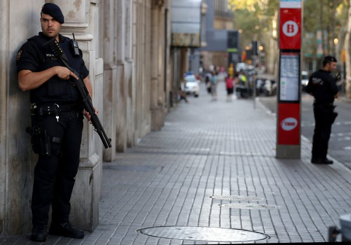 Armed Catalan Mossos d'esquadra officers stand guard at Las Ramblas street where a van crashed into pedestrians in Barcelona, Aug. 18.