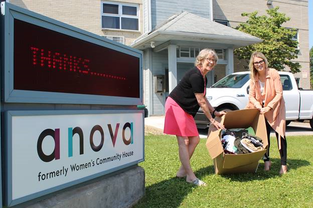 Anova executive director Kate Wiggins and Brescia's director of communications and external relations Colleen Aguilar hold a box filled with clothing donations.