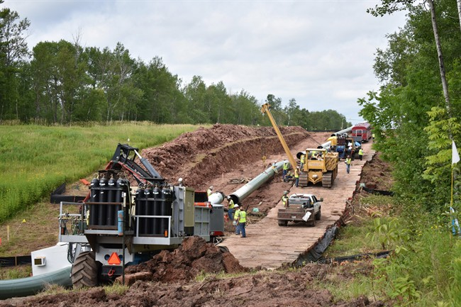 In this July 25, 2017, photo provided by Wisconsin Public Radio, crews begin work on the Wisconsin segment of Enbridge Energy's Line 3 near Superior, Wis.