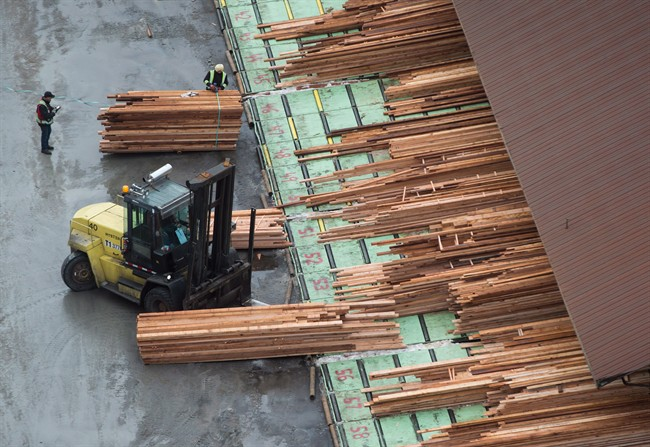 Workers sort and move lumber at the Delta Cedar Sawmill in Delta, B.C., on Friday January 6, 2017.