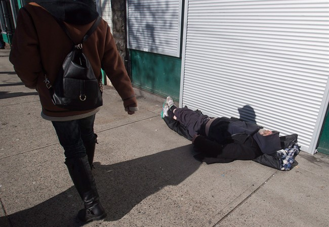 A woman walks past a man sleeping on the street in the Downtown Eastside of Vancouver, February 2017.