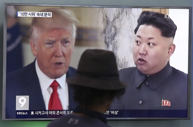 A man watches a television screen showing U.S. President Donald Trump, left, and North Korean leader Kim Jong-un.