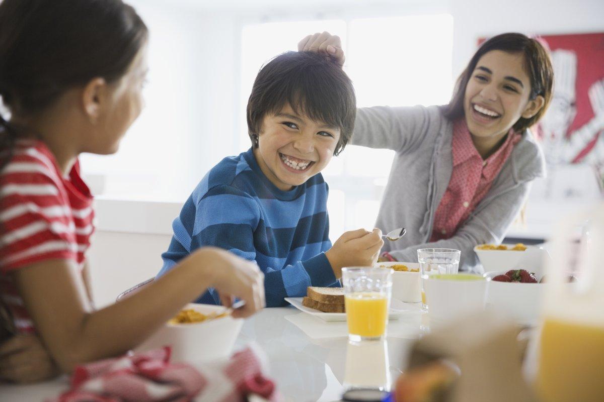 Playful siblings having breakfast together.
