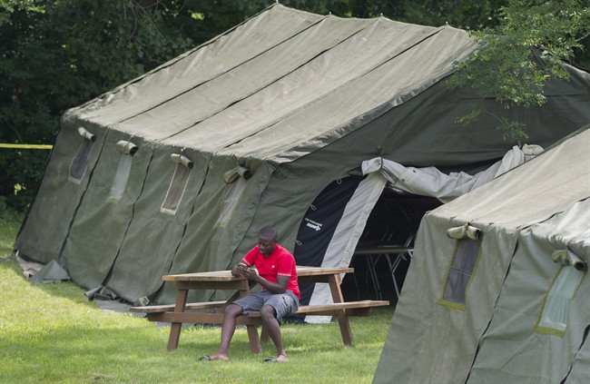 An asylum seeker checks his phone next to a tent at the Canada-United States border in Lacolle, Que.