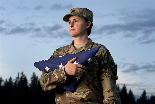 In this Aug. 28, 2015 file photo, Capt. Jennifer Peace, a transgender soldier,  holds a flag as she stands for a photo near her home in Spanaway, Wash.