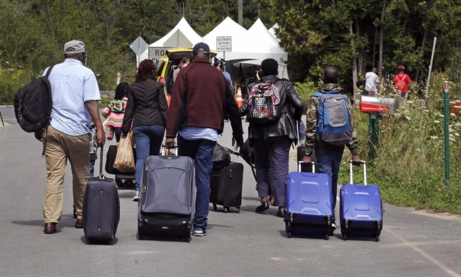 A family from Haiti approach a tent in Saint-Bernard-de-Lacolle, Quebec, stationed by Royal Canadian Mounted Police, as they haul their luggage down Roxham Road in Champlain, N.Y., Monday, Aug. 7, 2017.