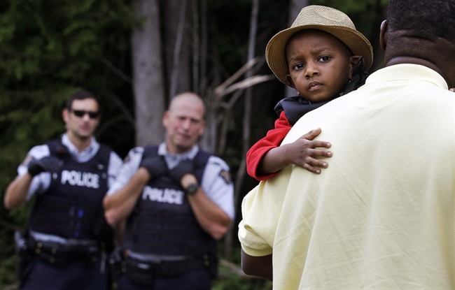 A Haitian boy holds onto his father as they approach an illegally crossing point, staffed by Royal Canadian Mounted Police officers, from Champlain, N.Y., to Saint-Bernard-de-Lacolle, Quebec, Monday, Aug. 7, 2017. Seven days a week, 24-hours a day people from across the globe are arriving at the end of a New York backroad so they can walk across a ditch into Canada knowing they will be instantly arrested, but with the hope the Canadian government will be kinder to them than the United States.
