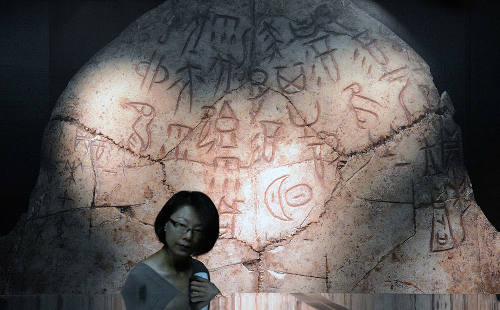 """A woman walks past an enlarged picture of Oracle bones script from 1,200 BC during an exhibition about """"King Wu Ding and Lady Hao: Art and Culture of the late Shang Dynasty"""" on display at the National Palace Museum in Taipei."""