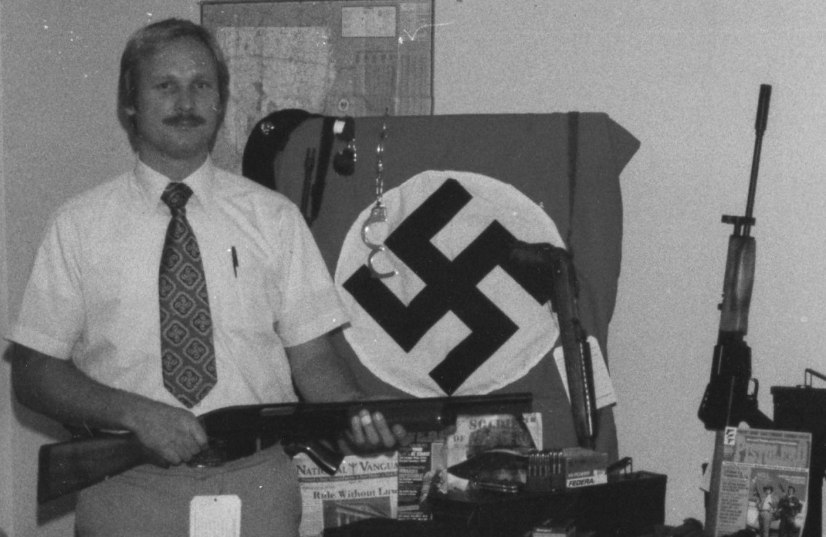 ATF agent John Osburg with weapons and flag seized in 1981 from Canadian and U.S. racists planning Operation Red Dog, a coup on the island of Dominica.