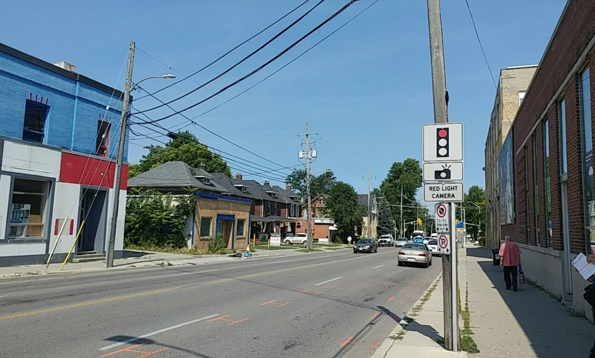 A sign warns drivers about a red-light camera, installed at the intersection of Adelaide St. and Queen's Ave. The intersection's red light camera caught more infractions than any other in the city.