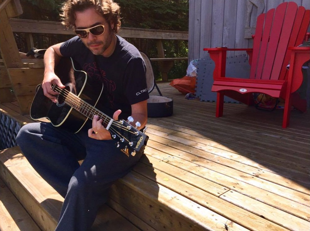 Adam Clarke plays a guitar at his home. He is turning part of a fallen tree from the intense Montreal thunder storm into a guitar.