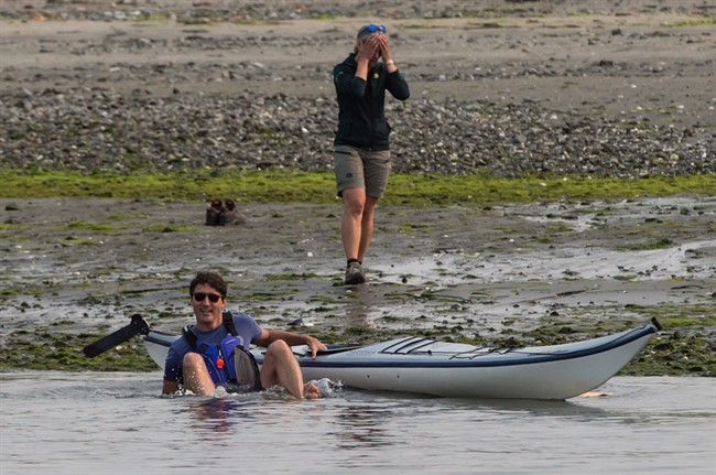 A Parks Canada staff member, back, reacts after Prime Minister Justin Trudeau fell into the water while trying to get into a kayak at Sidney Spit in the Gulf Islands National Park Reserve, east of Sidney, B.C., on Saturday August 5, 2017.