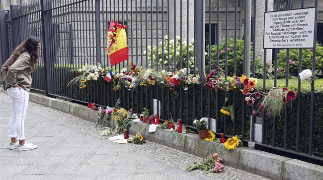 A woman looks at the symbols of condolence people have laid down for the victims of the terror attacks that killed 14 people and wounded over 120 in Barcelona , Spain, in front of the Spanish embassy in Berlin, Germany, Monday, Aug. 21, 2017.
