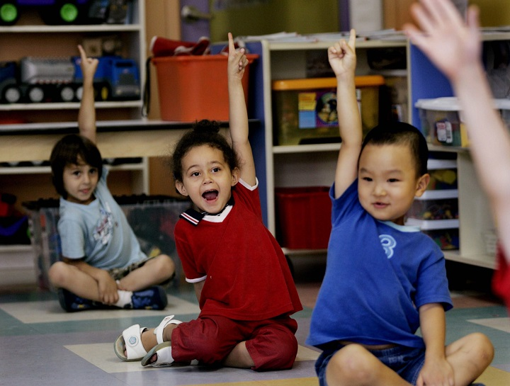 In this file photo, children put up their hands for ice cream at a daycare centre  in Montreal.