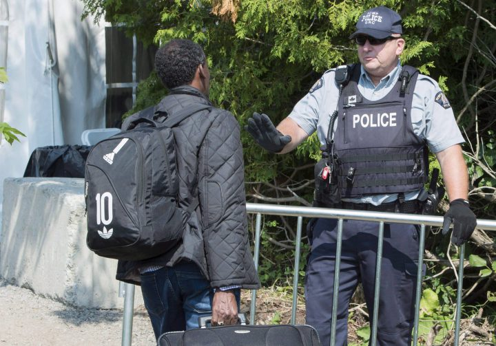 An asylum seeker, claiming to be from Eritrea, is questioned by an RCMP officer as he crosses the border into Canada from the United States Monday, August 21, 2017 near Champlain, N.Y.