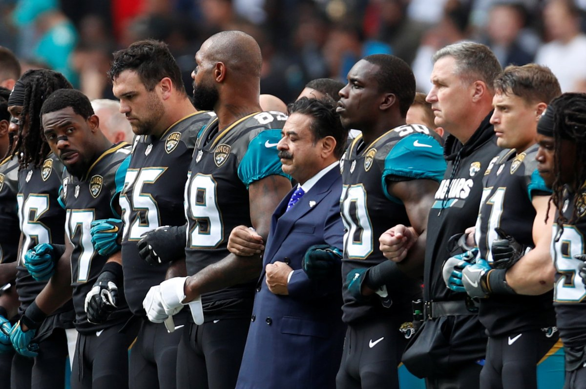 Jacksonville Jaguars owner Shahid Khan links arms with players during the national anthems before the match.