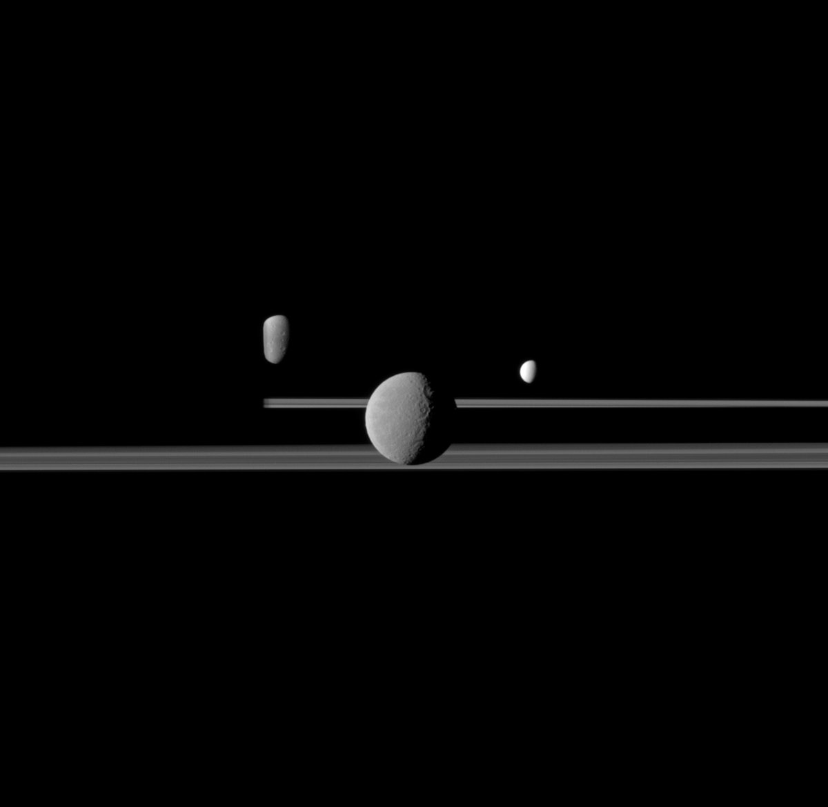The Cassini spacecraft observes three of Saturn's moons set against the darkened night side of the planet. Rhea, Enceladus and Dione.