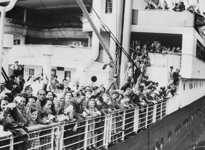 A crowd of German-Jewish refugees aboard the MS St. Louis ocean liner wave as they arrive in Antwerp, Belgium, after wandering the Atlantic for thousands of miles.