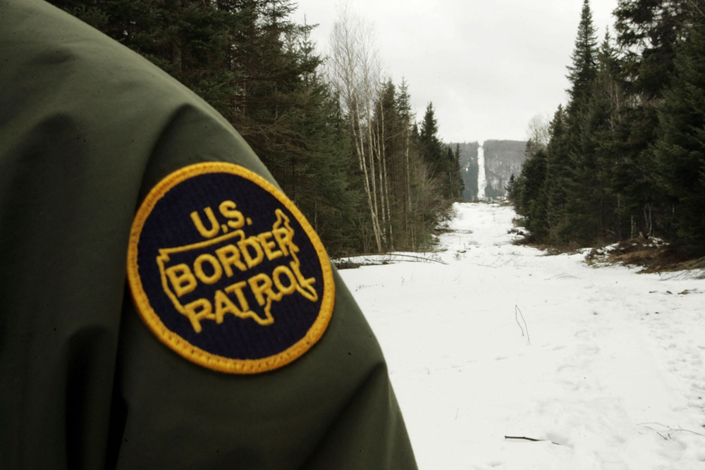 A U.S. Border Patrol agent stands along the boundary marker cut into the forest near Beecher Falls, Vermont in this file image.