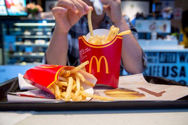 A girl eats fries in a McDonald's restaurant.