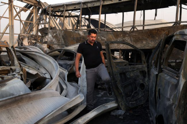 A man looks at the damage after gunmen and suicide car bombers killed dozens of people in two assaults claimed by Islamic State (IS) group jihadists near the southern Iraqi city of Nasiriyah on September 14, 2017.