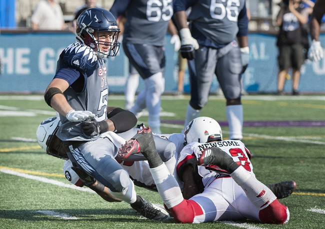 Montreal Alouettes quarterback Drew Willy, centre, is pulled down by Ottawa Redblacks' Avery Ellis, left, and Jonathan Newsome during second half CFL football action in Montreal, Sunday, September 17, 2017.