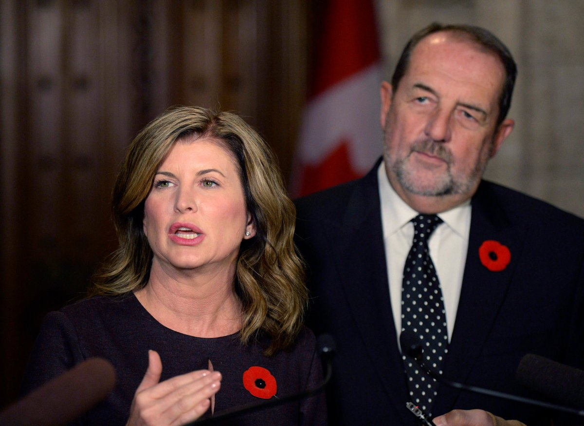 Former interim Conservative leader Rona Ambrose speaking to reporters following the tabling of the Fall Economic Statement, as fomer Conservative MP Denis Lebel looks on, on Parliament Hill, Tuesday, Nov. 1, 2016 in Ottawa.