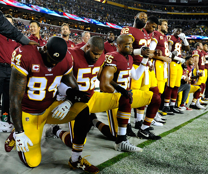 Washington Redskins teammates take a knee during the playing of the national anthem before their game against the Oakland Raiders at FedEx Field.