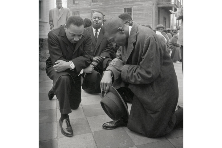 Civil rights leader Martin Luther King Jr. kneels with a group in prayer prior to going to jail in Selma, Alabama.