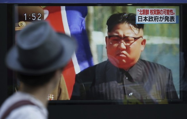 FILE - In this Sept. 3, 2017, file photo, a man in Tokyo watches a TV news program on a public screen showing an image of North Korean leader Kim Jong Un while reporting North Korea's possible nuclear test.