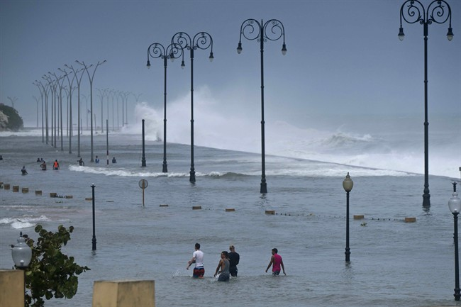 Residents walk on Havana's sea wall as the ocean crashes into it, after the passing of Hurricane Irma in Cuba, Sept. 10, 2017.