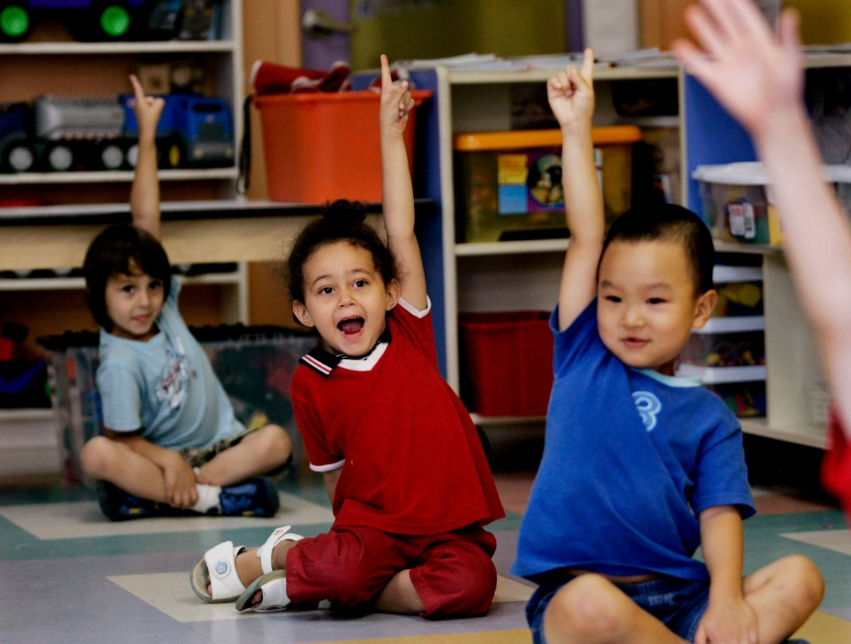 Children put up their hands for ice cream at a daycare centre  in Montreal.