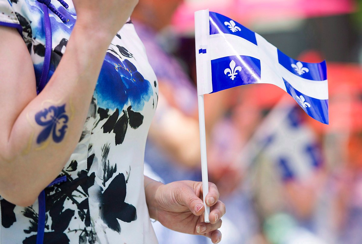 A woman holds a Quebec flag.
