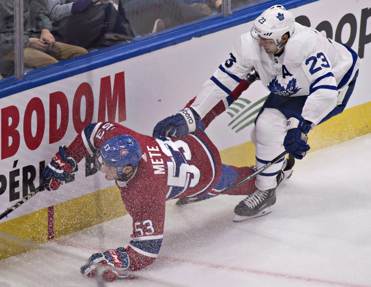 Montreal Canadiens' Victor Mete is tripped by Toronto Maple Leafs' Eric Fehr during second period NHL pre-season action Wednesday, September 27, 2017 in Quebec City.There is a youth movement on the Canadiens, as junior-age defenceman Mete, rookie Charles Hudonand centre Jacob De La Rose all are expected to at least start the NHL season in Montreal. THE CANADIAN PRESS/Jacques Boissinot.