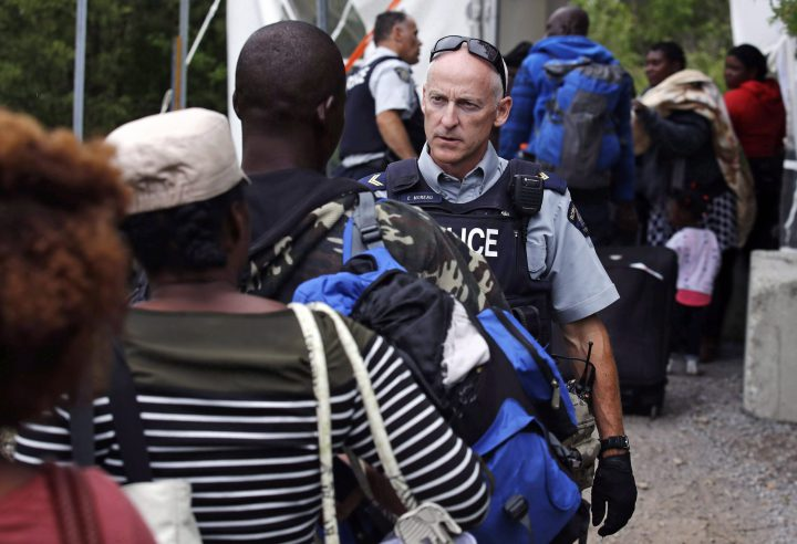 An RCMP officer standing in Saint-Bernard-de-Lacolle, Que., advises migrants that they are about to illegally cross from Champlain, N.Y., and will be arrested, Monday, Aug. 7, 2017. A spokesman for Public Safety Minister Ralph Goodale says an RCMP questionnaire that singled out Muslim asylum seekers has been deemed inappropriate and taken out of circulation. THE CANADIAN PRESS/AP/Charles Krupa.