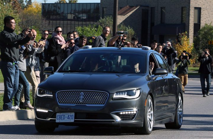 People watch as an autonomous car drives down an Ottawa street as the City of Ottawa and Blackberry QNX demonstrate the vehicle on Oct. 12, 2017.