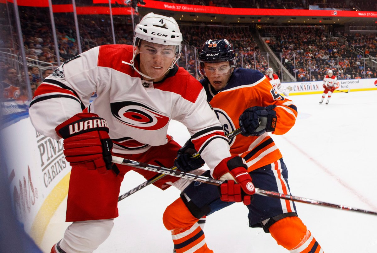 Carolina Hurricanes' Haydn Fleury (4) and Edmonton Oilers' Kailer Yamamoto (56) battle in the corner during second period NHL action in Edmonton, Alta., on Tuesday October 17, 2017.