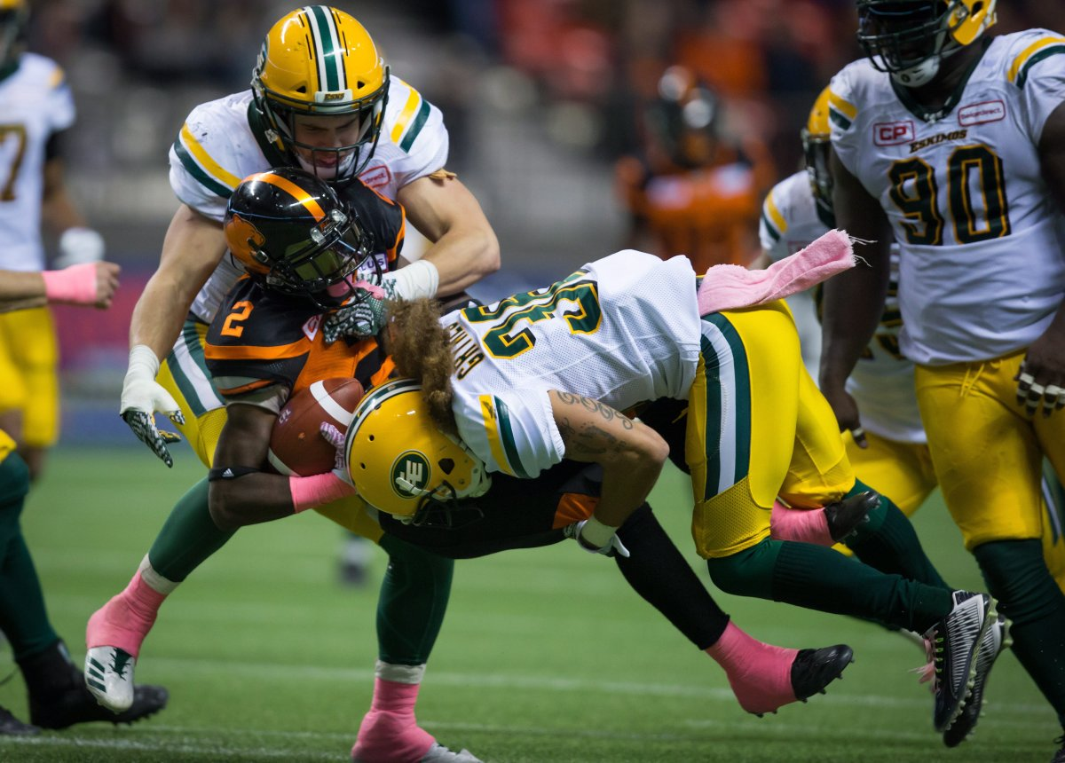 Edmonton Eskimos' Adam Konar, back left, and Aaron Grymes, right, tackle B.C. Lions' Chris Rainey (2) during the second half of a CFL football game in Vancouver, B.C., on Saturday October 21, 2017.