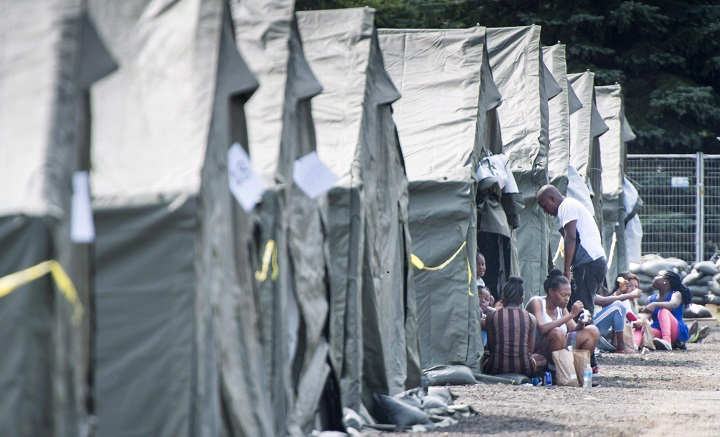 Asylum seekers sit in front of their tent in a temporary camp, Tuesday, August 15, 2017, near Saint-Bernard-de-Lacolle, Que.