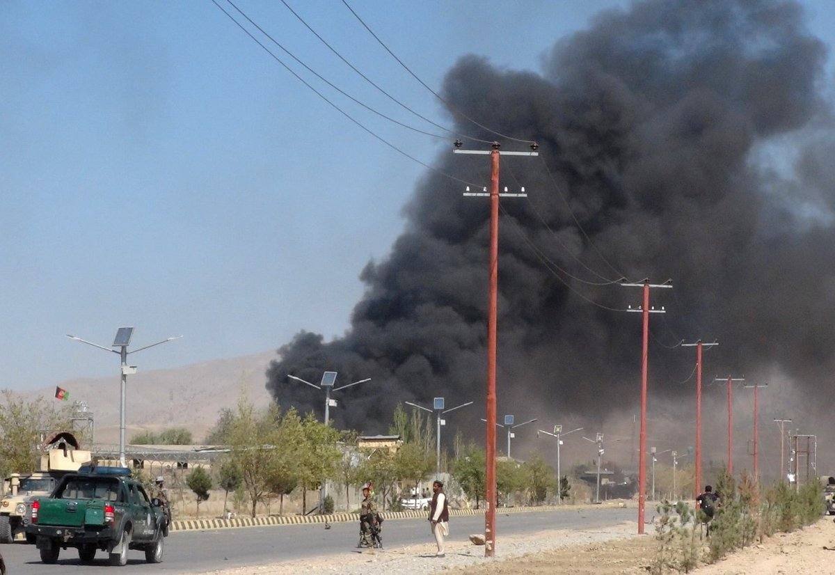 Smoke rises from police headquarters while Afghan security forces keep watch after a suicide car bomber and gunmen attacked the provincial police headquarters in Gardez, the capital of Paktia province, Afghanistan Oct. 17.