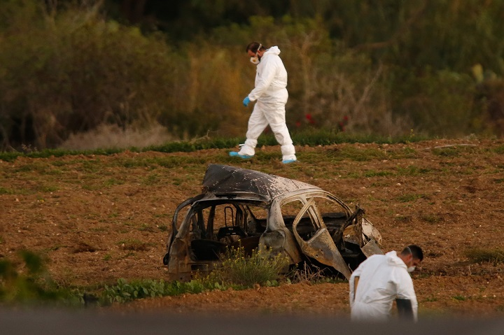 Forensic experts search for clues in a field after a powerful bomb blew up a car and killed investigative journalist Daphne Caruana Galizia in Bidnija, Malta, on October 16, 2017.