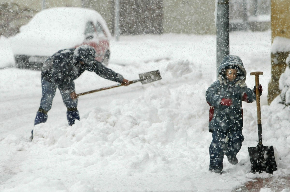 A man and a child use shovels to remove snow at the door of their house.