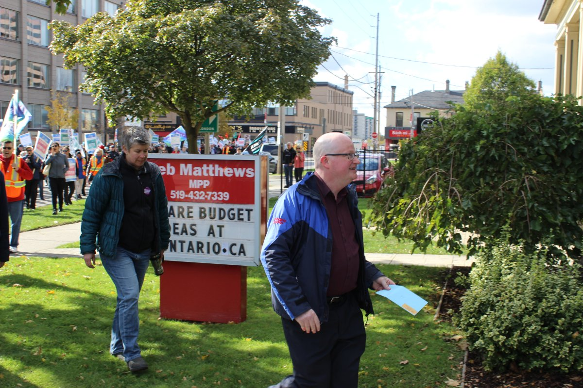 Darryl Bedford, the president of OPSEU local 110, approaches Deb Matthews' constituency office in London with a letter, followed by OPSEU bargaining unit chair, JP Hornick.