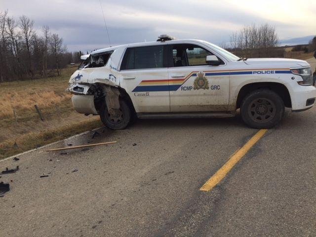 A suspect in a stolen tractor rams a police cruiser during a roadblock.