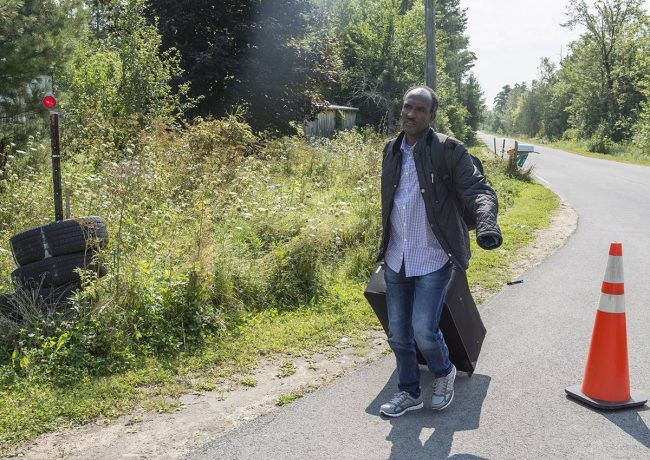 An asylum seekers, claiming to be from Eritrea, walks up to cross the border into Canada from the United States Monday, August 21, 2017 near Champlain, N.Y.