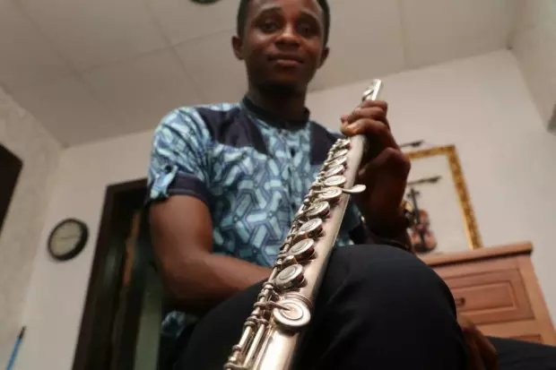 Ogo-Oluwa Sobukola, a Nigerian flutist, poses with the instrument that has brought him to Canada.