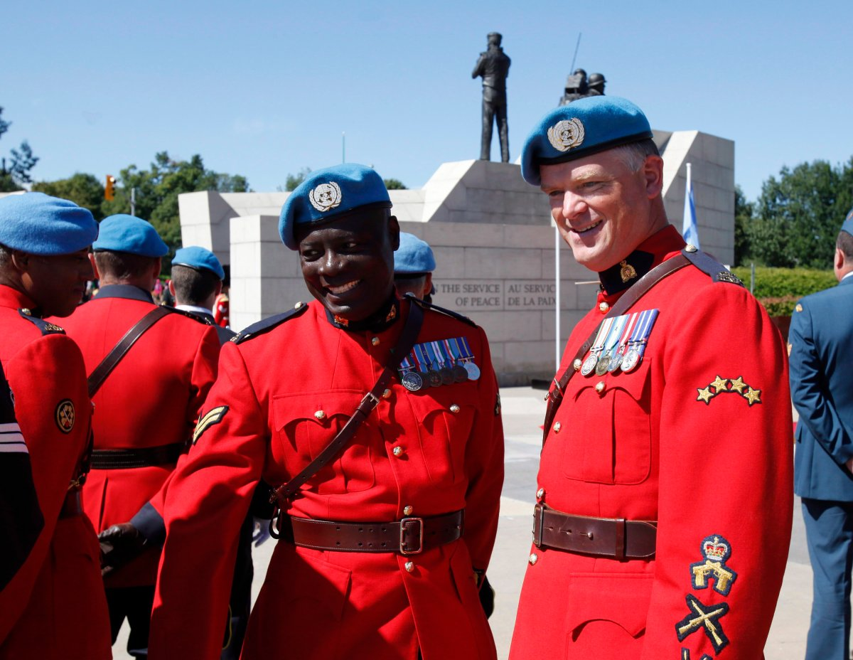 RCMP Cpl. Kofi Gordon, left, who served as a peacekeeper in the Democratic Republic of the Congo and Haiti, and Sergeant Ron Rose, who served as a peacekeeper in Haiti, pose for photos at the National Peacekeeping Monument.