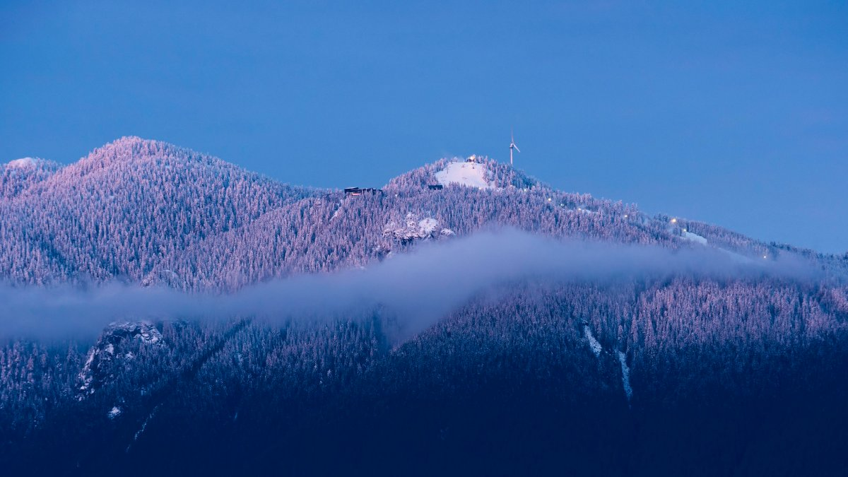Sunset colours light up fresh snow on the peaks of Vancouver's North Shore Mountains, including the Grouse Mountain ski runs, North Vancouver, B.C., February 2, 2016.