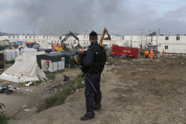 In this Oct. 26, 2016 file photo, a police officer stands guard as workers dismantle structures of the makeshift refugee camp known as the 'Jungle' in Calais, France.
