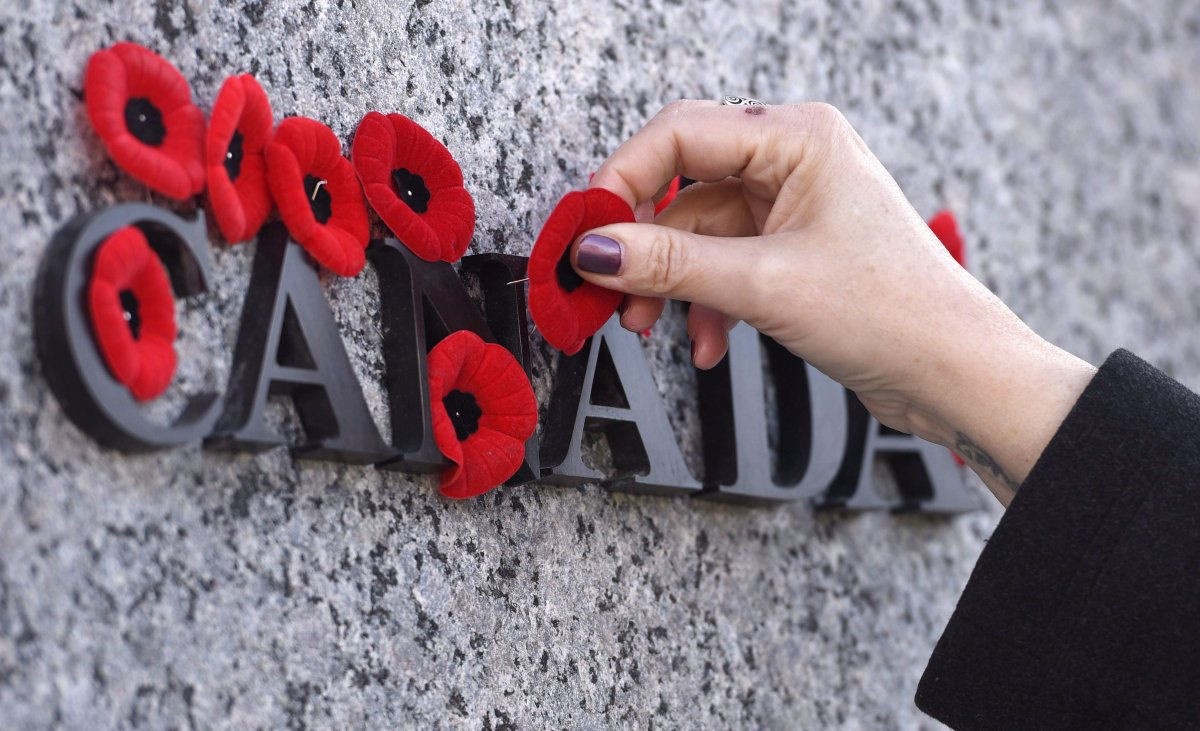 People place poppies over lettering in the National War Memorial during the National Remembrance Day ceremony in Ottawa on November 11, 2016.